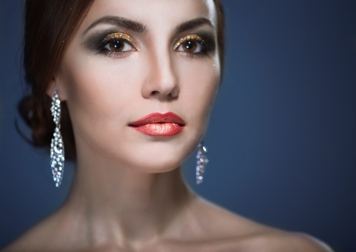 christmas eye makeup, in gold with smokey effect, worn by a pale woman, with brunette hair, styled in a bun, glossy orange lipstick, and sparkling silver earrings