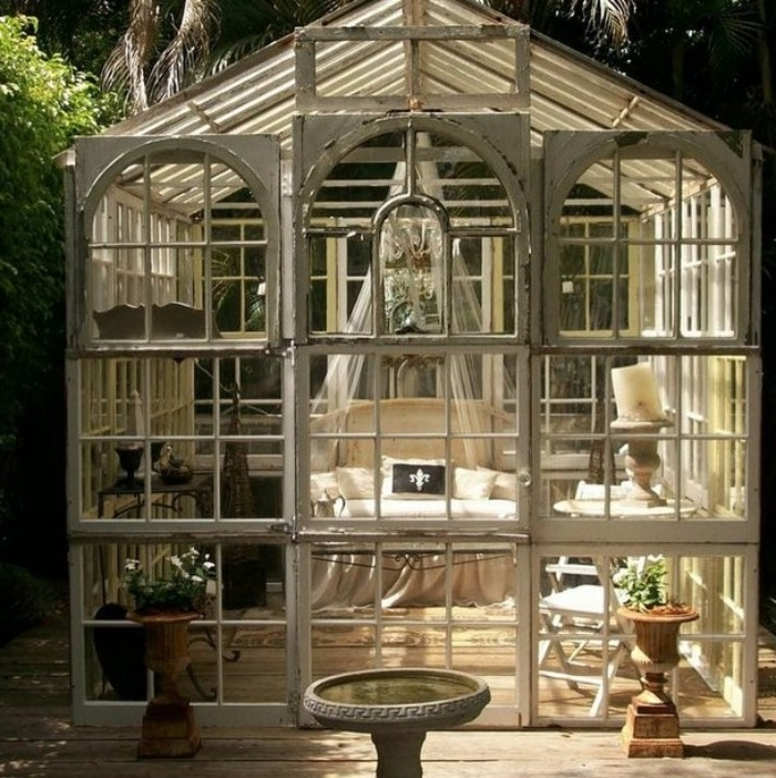 antique greenhouse style shed, with lots of glass panels, and white frames, containing a small cream sofa, with a sheer white baldachin