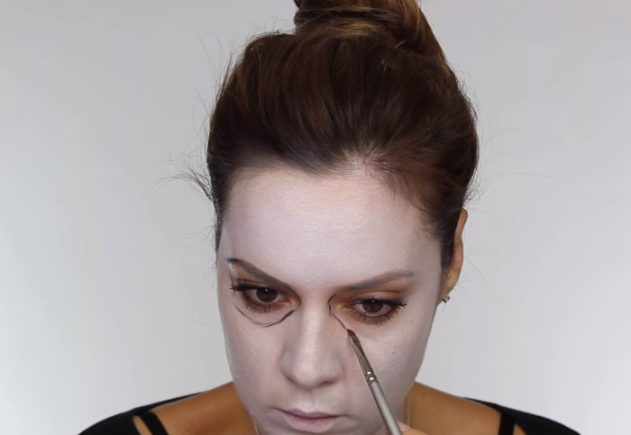 brunette woman with face covered in white paint, using a small brush, to outline her eyes, skeleton face paint, steb by step