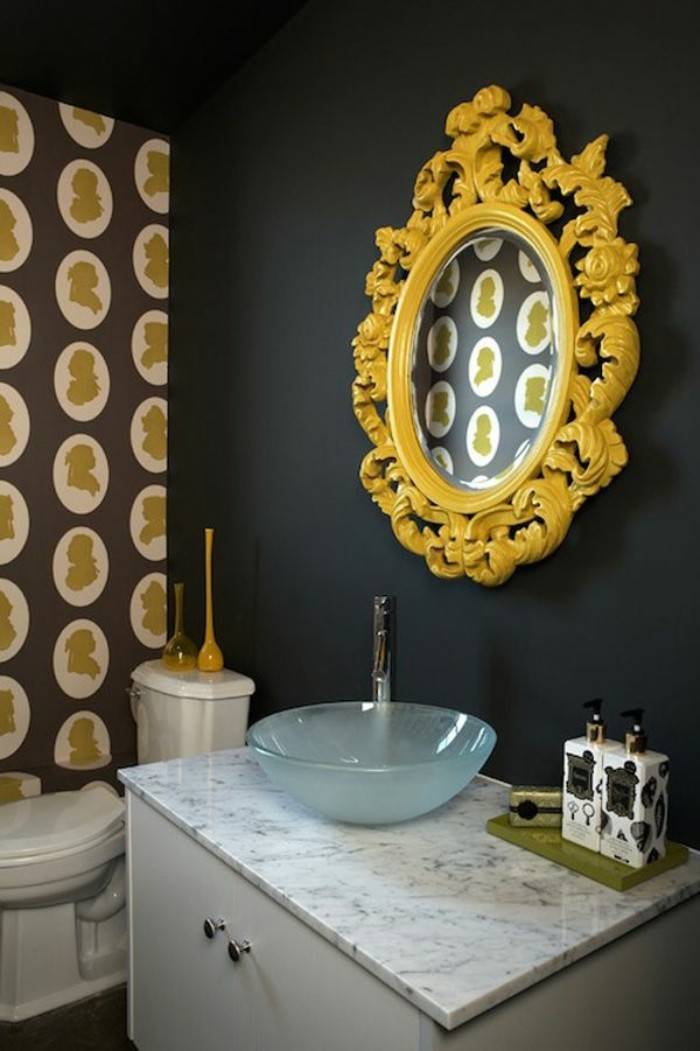 baroque frame in yellow, around an oval mirror, mounted on a black wall, small bathroom paint colors, over a white cupboard, with a marble countertop, and a small sink