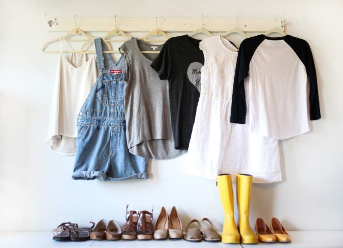 dungarees made of blue denim, a cami top, two t-shirts, a jumper and a white lace mini dress, capsule wardrobe planner, hanging over six pairs of shoes, and a pair of rubber yellow boots