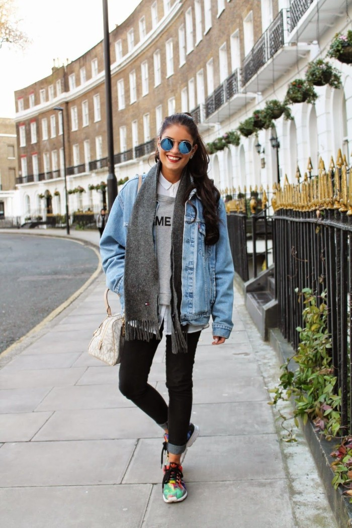 capsule closet, smiling young brunette woman, wearing black skinny jeans, a white shirt, a pale grey jumper, and an oversized denim jacket