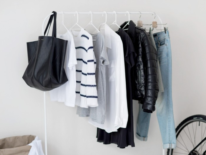light blue jeans, black winter jacket, white shirt and grey t-shirt, striped jumper and white t-shirt, and a black tote bag, hanging on a clothes rack, capsule wardrobe