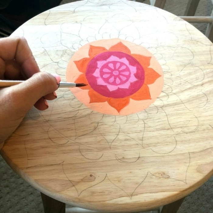hand holding a paint brush, over a round wooden surface, featuring a pencil mandala sketch, diy room decor, with a small area colored in pink, orange and red