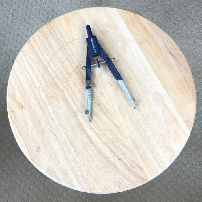 compasses placed on top of a round wooden stool, diy room decor, several circles drown on top of it, in plain pencil
