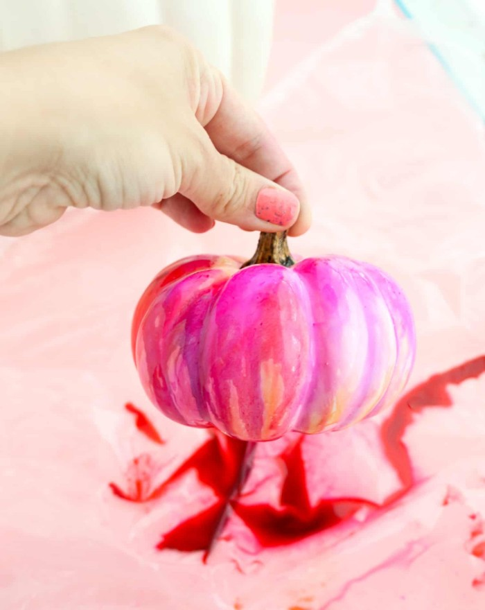 hand with pink nail polish, holding a small fake pumpkin, painted in pink, red and orange, halloween pumpkin decorations, over a piece of plastic with red paint