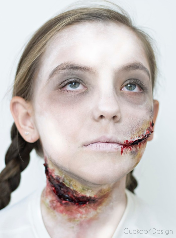 strongly illumianted image of a young girl, her face painted to look like a zombie, facepaint ideas, gory realistic scars, pale white skin