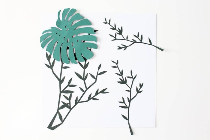 creating a 3D paper collage, diy bedroom décor, sticking a palm leaf-shaped, green paper cutout, on top of a few branch-like paper shapes, using adhesive strips