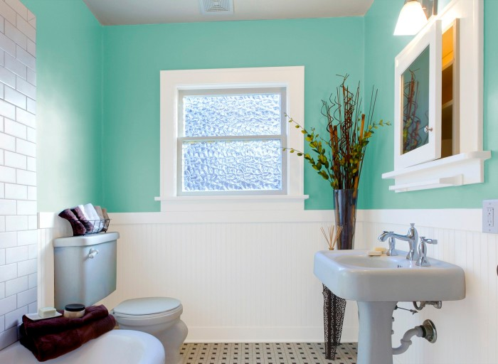 plants in a tall vase, decorating a teal blue bathroom, with white wooden paneling, and baby blue sink and toilet set, small bathroom paint colors, small window and white subway tiles