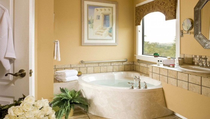 corner bathtub in cream, inside a bathroom with pale, pastel orange walls, decorated with beige tiles, white roses and a potted fern