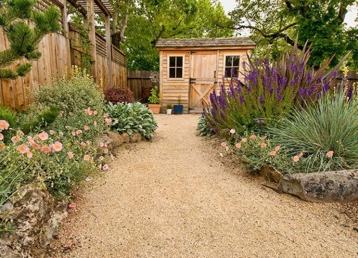 she shed ideas, small wooden hut, with two windows, inside a garden, with lots of different flowers, and a pebbled path