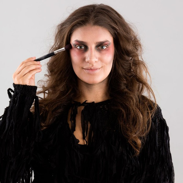 zombie face paint, tutorial with photos, smiling brunette woman, dressed in black, putting pink blush, around her eyes, using a brush