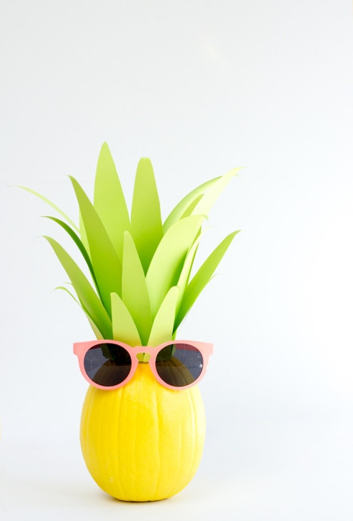 pumpkin painted in yellow, and decorated with light green, long paper cutouts, to make it look like a pineapple, diy bedroom décor, funny pink sunglasses