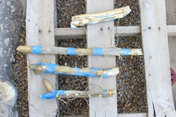 room makeover, with a diy hanging jewelry stand tutorial, one short piece of driftwood, spray-painted in metallic gold, near three other pieces, partially wrapped with blue masking tape