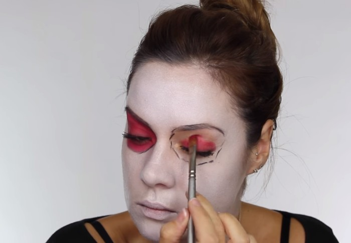 putting pink eye shadow, on the eyelids of a young woman, with face covered in white paint, skeleton face paint, step by step tutorial