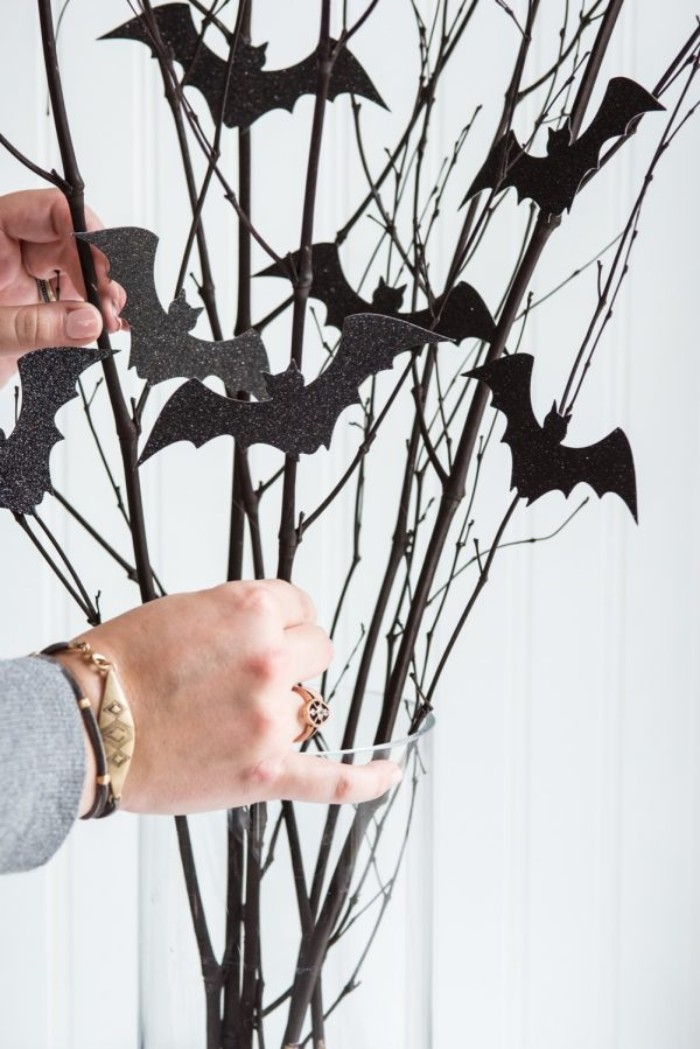 putting the ready halloween decoration, consisting of thin dried branches, with small glittering black bat shapes, in a clear glass vase