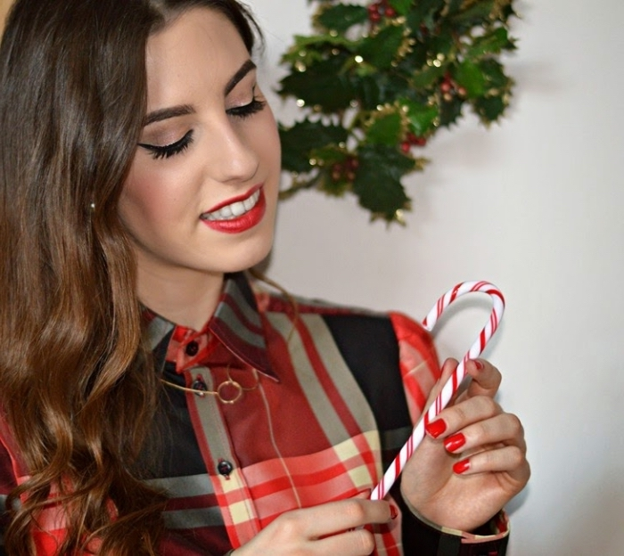 smiling young brunette woman, in a plaid shirt, wearing red lipstick, black eyeliner and fake lashes, and holding a candy cane