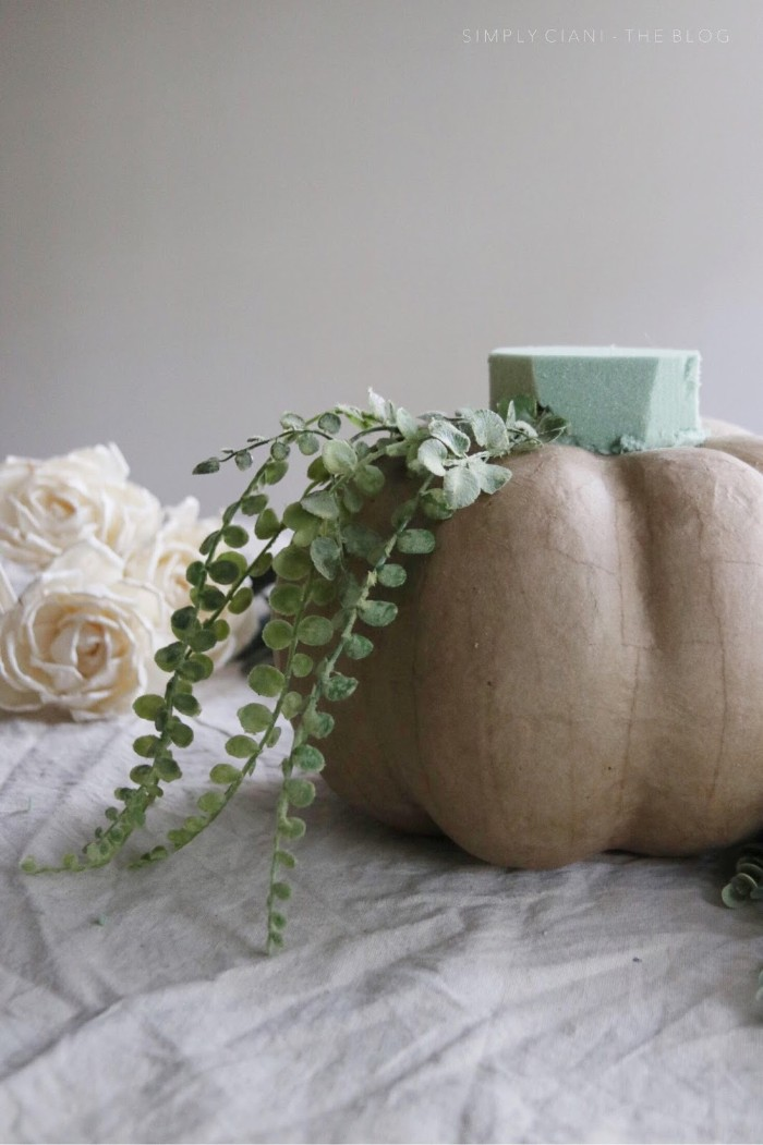 papier mache pumpkin in beige, dollar store crafts, with a mint green florist sponge on top, decorated with plastic green plants