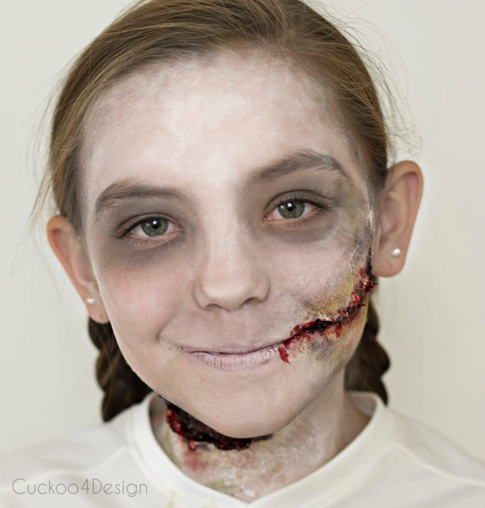 realistic bloody scars, created with special effects makeup wax, and faux blood, on the face of a smiling young girl, facepaint ideas