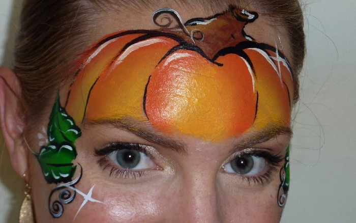 a different kind of witch face paint, pumpkin painted in orange and black, brown and white, with little green leaves, on the forehead of a young woman