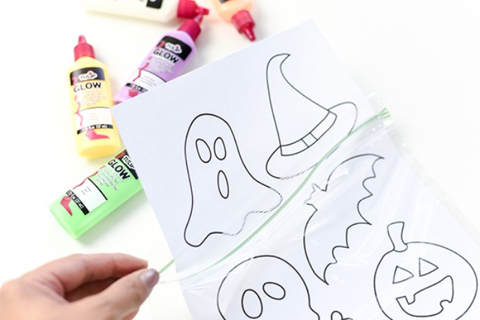 sheet of white paper, with simple drawings of halloween related objects, placed in a ziploc bag, held by a hand, with pale pink nail polish, halloween decorations diy, tubs of paint in the background