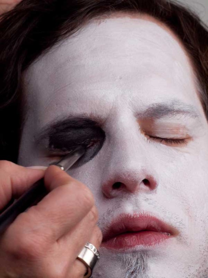 black eye shadow, applied onto the eyelid of a young man, wearing white paint on his face, clown face paint, step by step tutorial