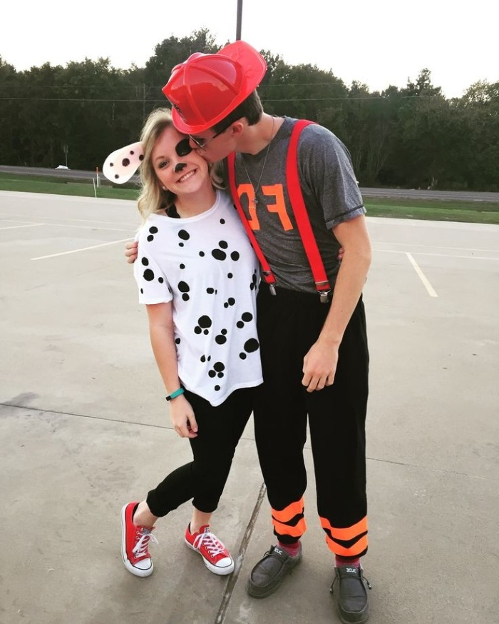 firefighter and dalmatian, funny couple halloween costumes, man with red hard hat, kissing the cheek of a young woman, in a white t-shirt with black spots, wearing face paint and puppy ears