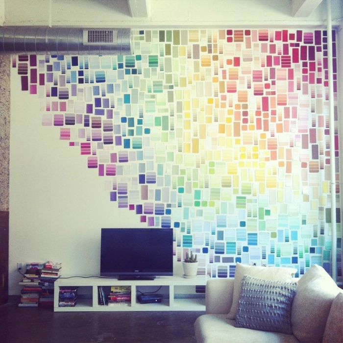 hundreds of colorful strips of paper, arranged like a rainbow, on a white wall, behind a TV, pale cream sofa nearby, handmade wall decoration