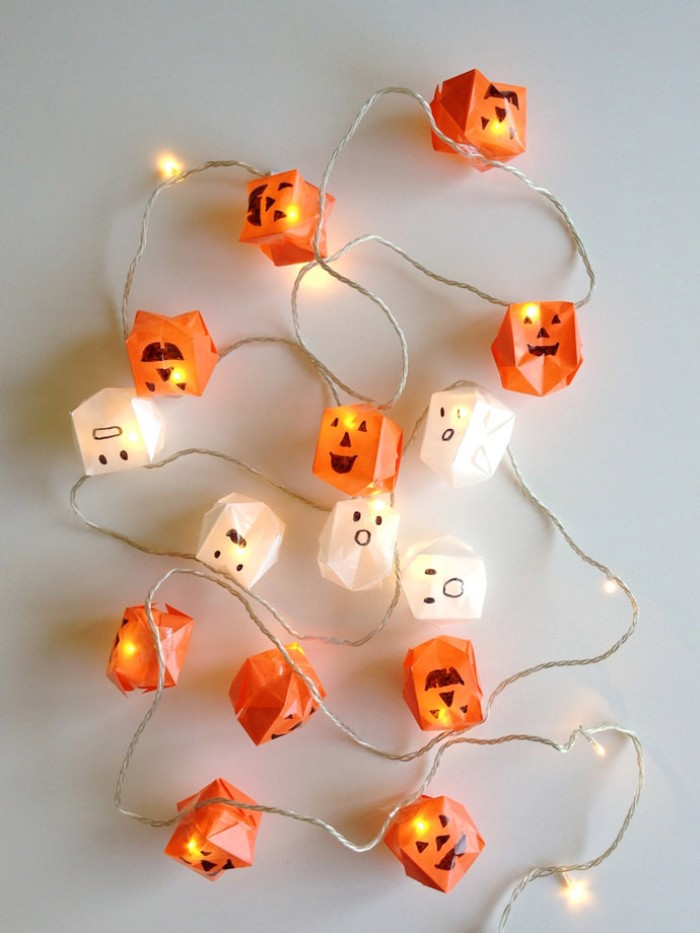 string lights decorated with paper origami shapes, in orange and white, made to look like jack-o-lanterns, and little ghosts