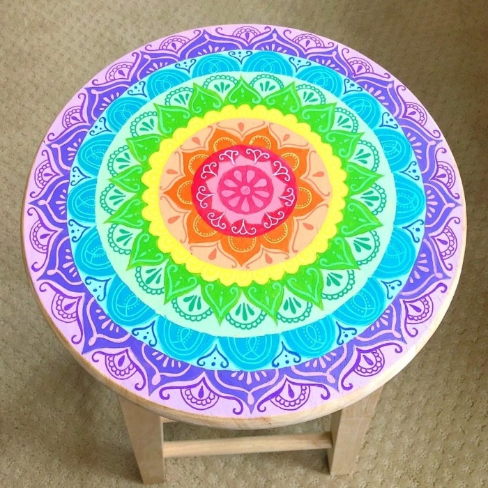 completed flower mandala drawing, in rainbow colors, decorated with white hand-drawn ornaments, diy room decor, on a round wooden stool