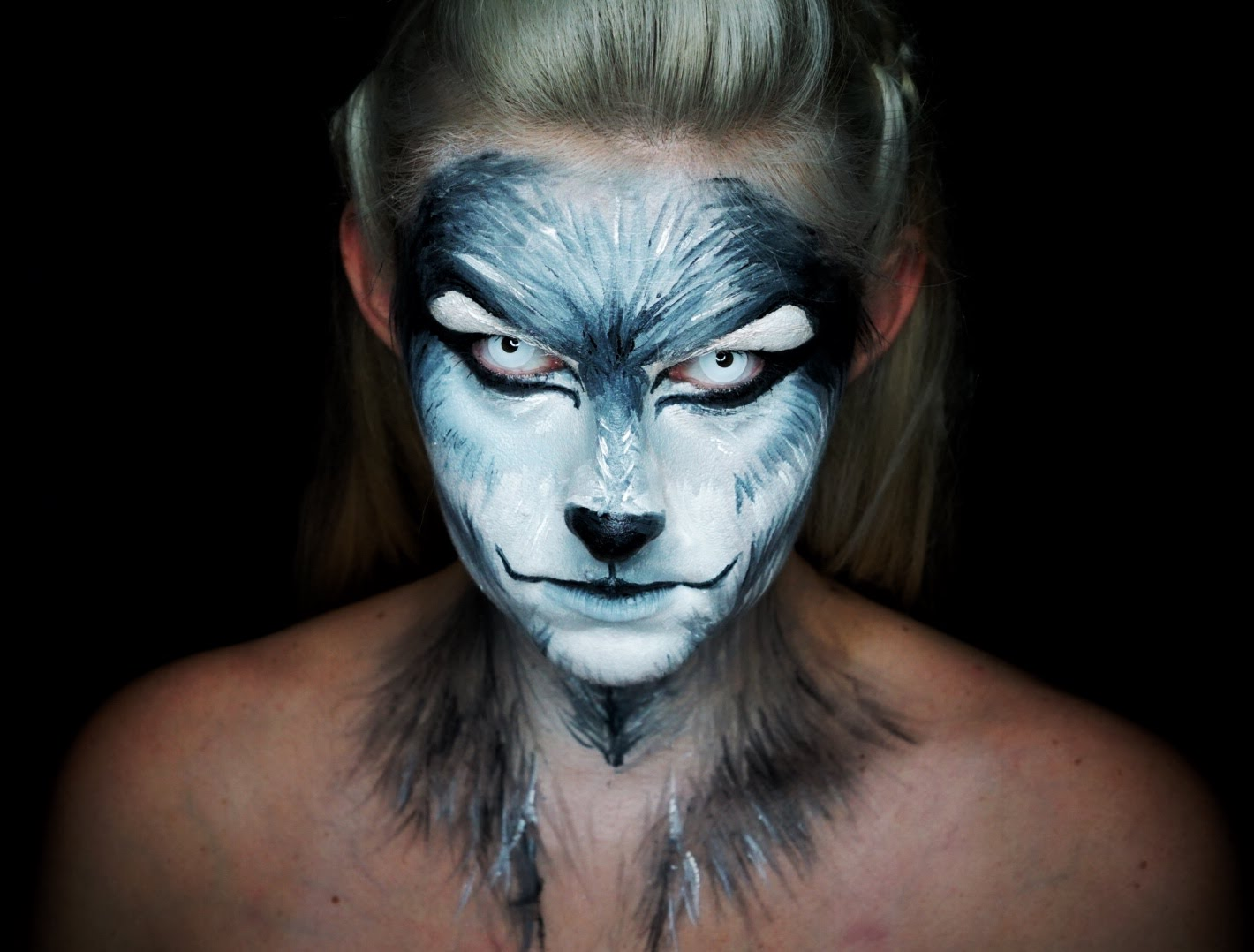 werewolf face paint, in white and grey, worn with pale blue contact lenses, by a blonde woman, halloween face paint