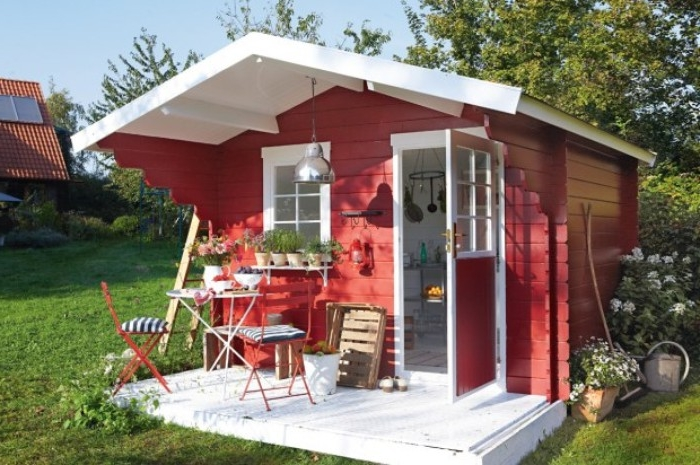 shed ideas, red and white structure, with an open door, and a small window, garden table and two chairs, standing in front of it