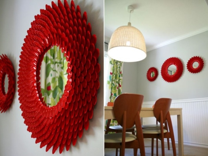 round mirrors with decorative frames, made from red plastic spoons, hung on the pale grey wall, of a dining room