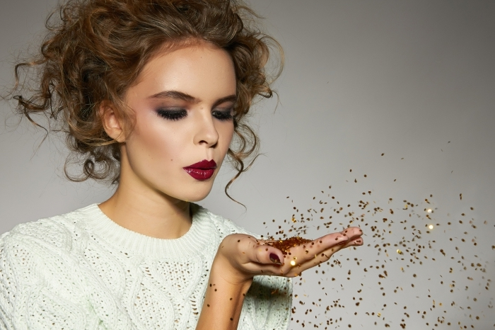 curly slim brunette woman, dressed in a white cable knit sweater, and wearing dark red lipstick, and smokey eye makeup, christmas makeup looks, blowing gold glitter, which she holds in the palm of her hand