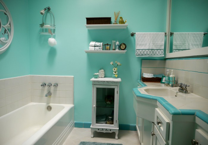 retro-style bathroom, with robin's egg blue walls, a white bathtub, and an antique white cupboard