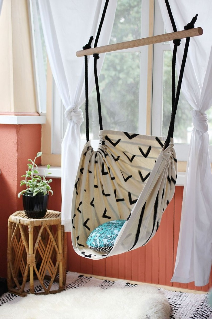 diys to do at home, pale cream hammock swing, with black pattern, hanging from the ceiling of a room, with pale pink walls, and salmon pink paneling