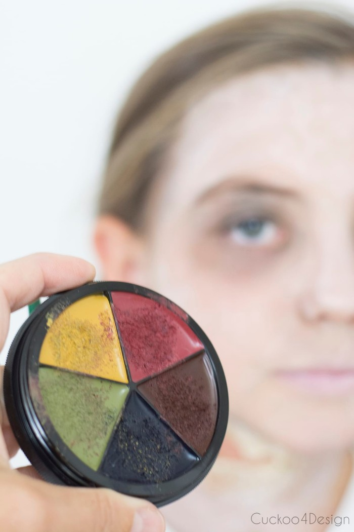 extreme close up of a paint palette, with yellow and red, green and black, and brown colors, scary face paint, child with a white face in the background