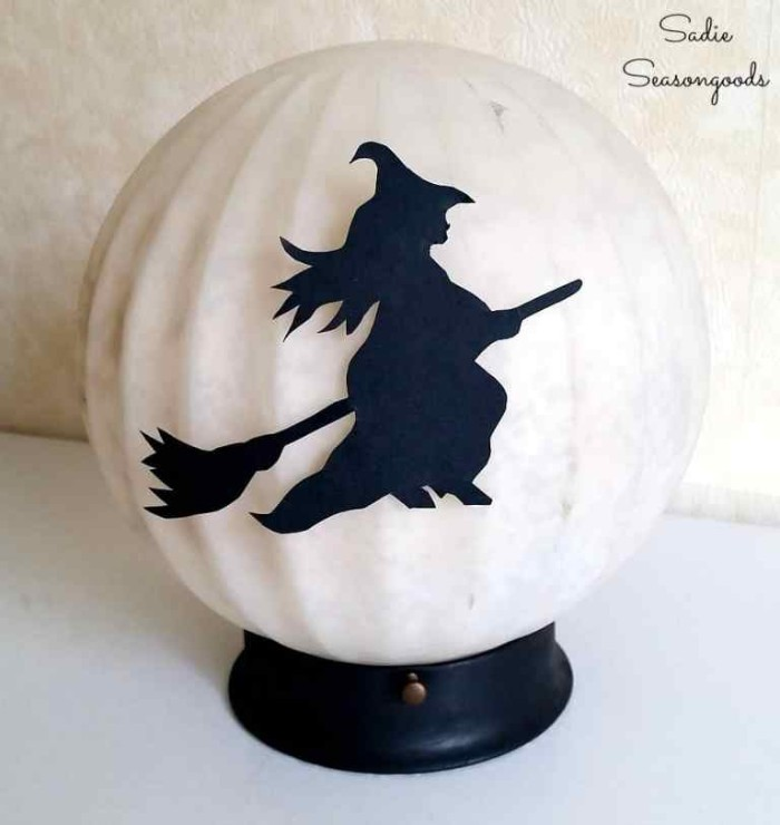 cream colored round lamp, on a small black plastic stand, decorated with a black cutout, shaped like a witch on a broom, halloween witch decorations, diy moon lamp