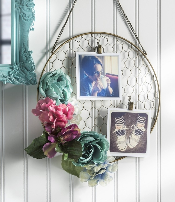 oval wall decoration, made from a metal hoop, and mesh net, and decorated with two photos, and some faux flowers