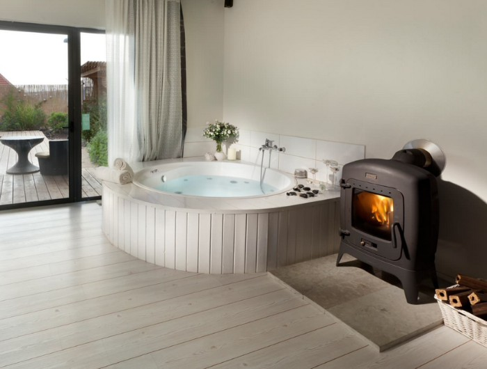 heater powered by wood, inside a room, with a light laminate floor, containing a hot tub, lined with white wood, master bath remodel, large window overlooking a garden