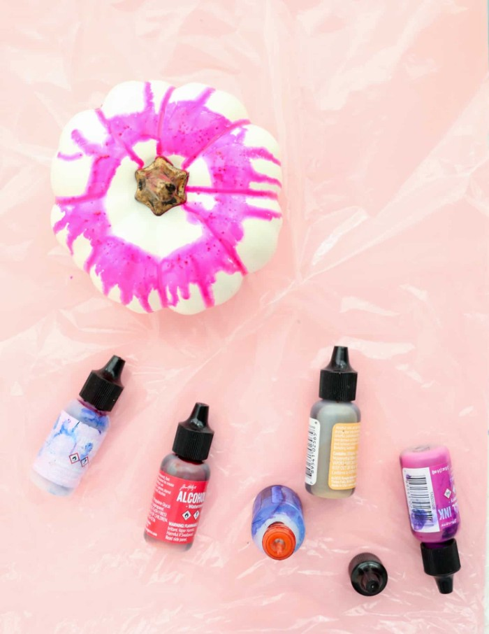 fuchsia pink paint, running down a small, fake white pumpkin, halloween pumpkin decorations, five small bottles, of liquid paint in different colors