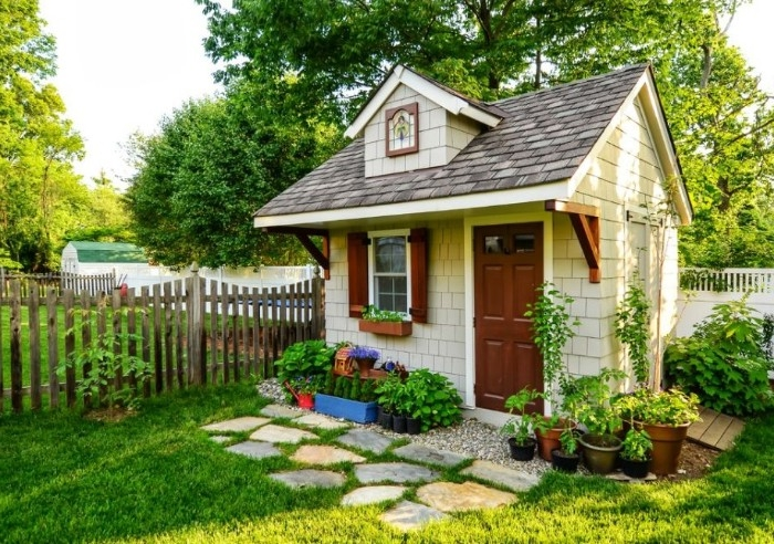 cottage style she shed, tiny house with a brown door, and a window with wooden shutters, inside a garden, with various potted plants