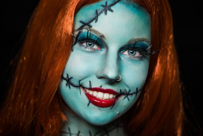 nightmare before christmas-inspired face paint, woman dressed like sally, in a ginger wig, wearing pale blue paint on her face, with black hand-drawn stitches, and glossy red lipstick
