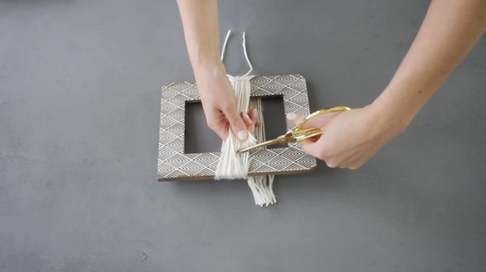 brown picture frame, with white details, and yarn wrapped around it, room makeover with a diy chandelier, hands with scissors, cutting the yarn free from the frame
