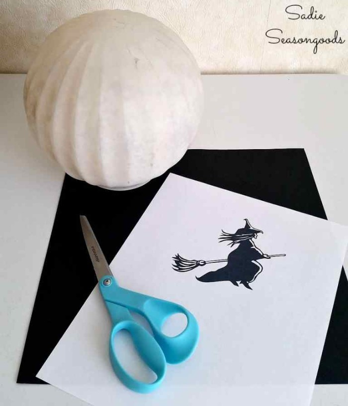 spherical white lamp, a sheet of black card, a pair of scissors, and a white piece of paper, with a simple drawing of a witch, in black and white, materials needed for making, halloween witch decorations