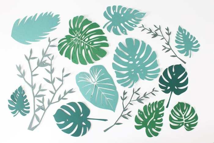 several branch- and palm leaf-shaped cutouts, in different shades of green, how to decorate a bedroom, placed on a white surface