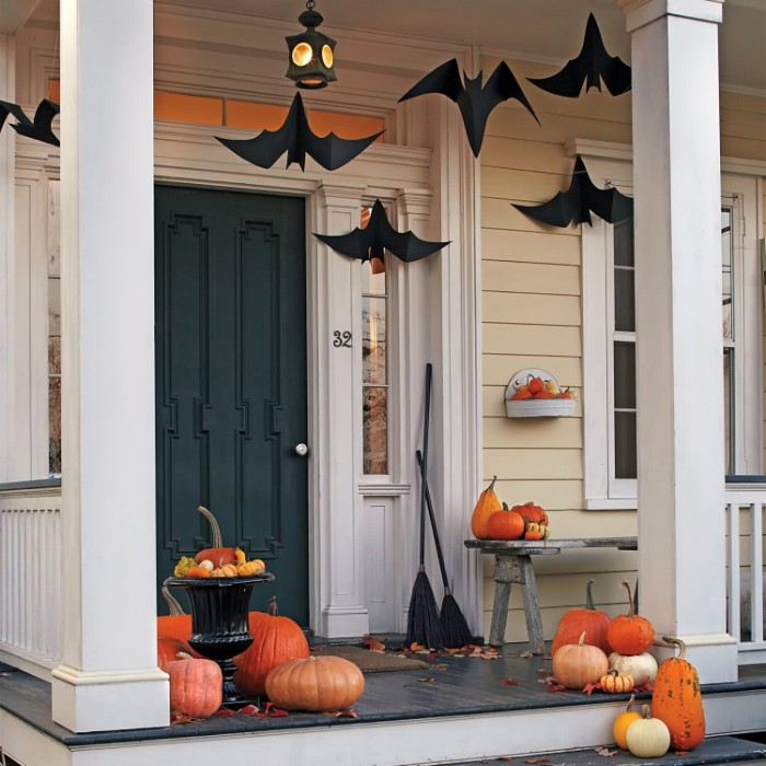 porch decorated with several pumpkins, in different shapes and sizes, halloween pumpkin decorations, black paper bats, hanging above them