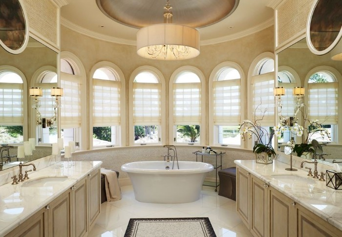 six windows inside a semi-round bathroom, with a cream, beige and white color palette, vintage style bathtub in white