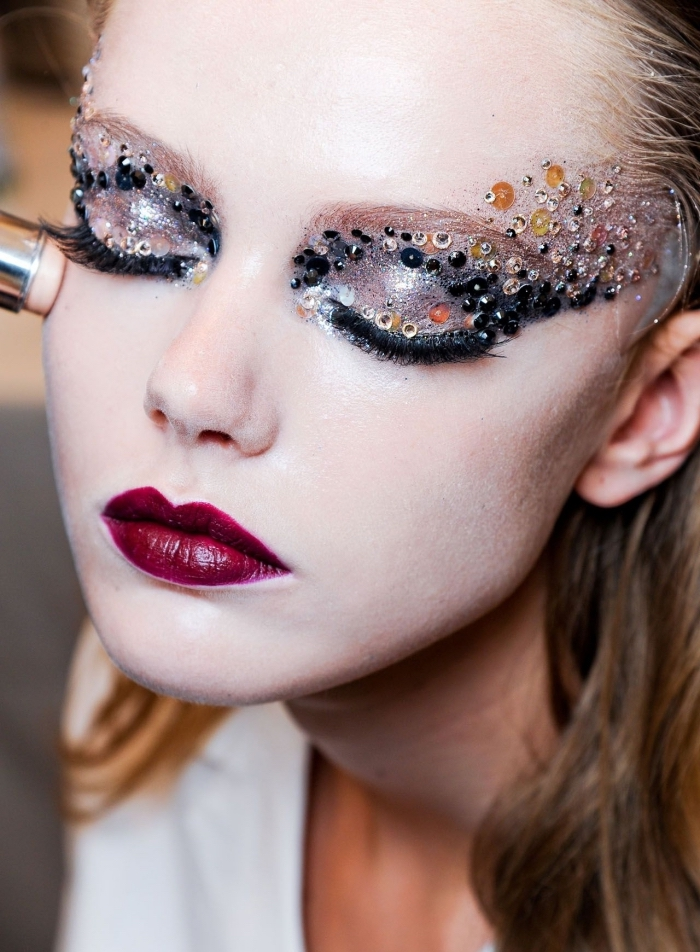 small beads in black, and silver and gold sequins, decorating the eyelids of a pale young woman, christmas eye makeup, with dark red lipstick, and silver eye shadow