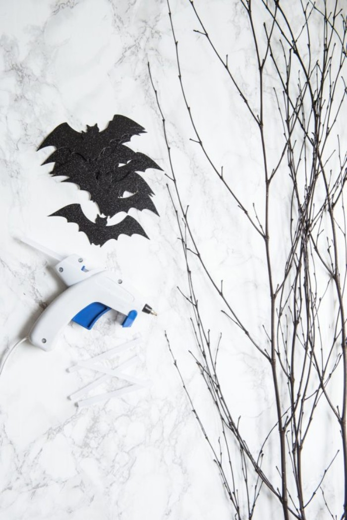 glue gun and several black, bat-shaped card cutouts in black, on a marble surface, near a bunch of thin, dried tree branches